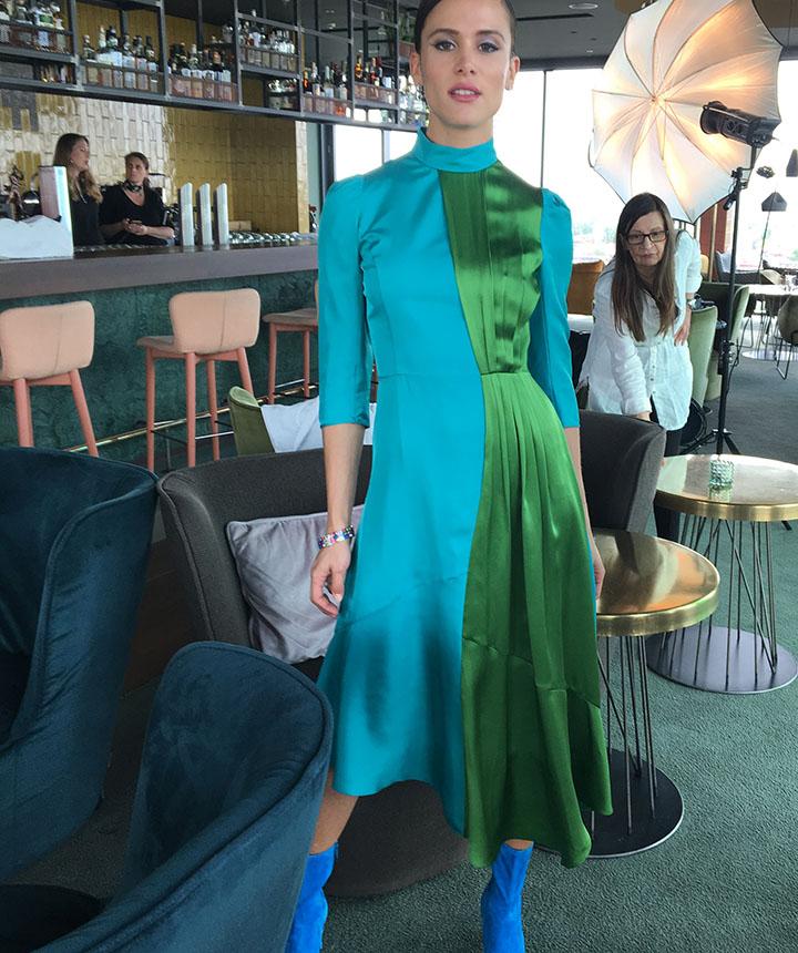 Karlla steht in der Bar Loft14 in einem grün-türkifarbenen Seidenkleid von Andrew GN