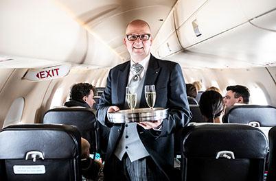 Butler schenkt im Flugzeug Champagner aus