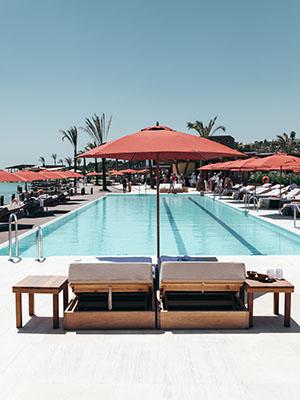 Sonnenschirme in der Farbe Terracotta stehen an einem Pool
