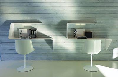 weiße Stühle vor weißen Schreibtischen an Wand